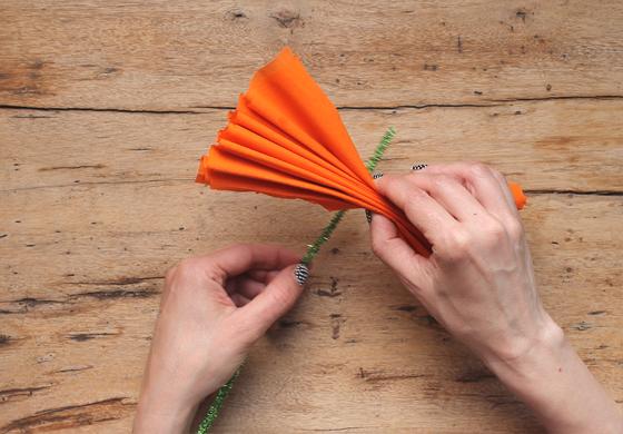 Colocando el cepillo destapacañerías alrededor de la flor de papel crepé